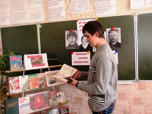 Учащийся Климовского аграрно-транспортного колледжа у выставки литературы в День памяти воинов-интернационалистов в России